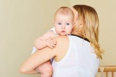 Baby mit blauen Augen in den Armen ihrer Mutter Das Konzept O Lizenzfreie Stockfotos