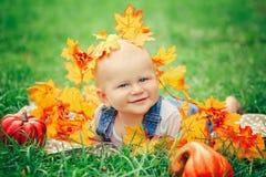 Baby mit blauen Augen im T-Shirt und in Jeansspielanzug, die auf Rasenflächewiese im gelben Herbstlaub liegen Stockfotografie