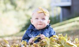 Baby mit Bogen im Kopf, der mit Blättern an einem Fall-Tag spielt Lizenzfreie Stockfotografie