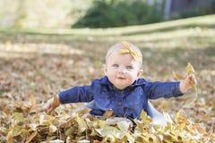 Baby mit Bogen im Kopf, der mit Blättern an einem Fall-Tag spielt Lizenzfreies Stockfoto