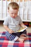 Baby mit Buch zu Hause Lizenzfreie Stockfotos
