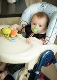 Baby mit dem soother, das im Stuhl für die Fütterung sitzt Lizenzfreies Stockbild