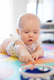 Baby mit den blauen Augen, die auf Matte am Boden spielen Lizenzfreie Stockfotos