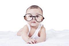 Baby mit den Gläsern, die auf Bett liegen Stockfotos