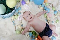 Baby mit den Häschenohren auf einem Ostern-Satz Stockfotografie
