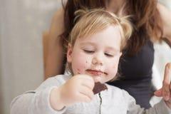 Baby mit der Mutter, die Schokolade isst Lizenzfreie Stockbilder