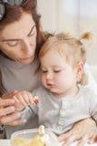 Baby mit der Mutter, die vom tupperware isst Lizenzfreies Stockbild