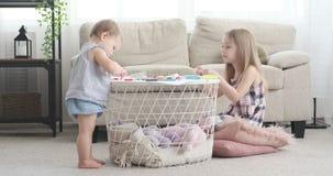 Baby mit der Schwester, die zu Hause kreative Kunst- und Handwerksarbeit erledigt stock footage