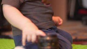 Baby mit einem soother im Mund, der auf dem Boden und neugierig der rührenden Linse einer alten Kamera sitzt Innenseitenansicht 4 stock video footage