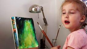 Baby mit einer Bürste zeichnet ein Bild stock video
