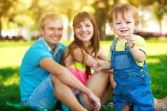 Lächelndes Baby mit Eltern in einem schönen Park Stockbilder