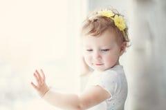 Baby mit gelben Blumen in ihrem Haar Stockfotos