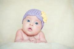 Baby mit gestricktem Hut mit Blume Stockbilder