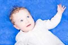 Baby mit großen blauen Augen auf blauer Decke Lizenzfreie Stockfotografie