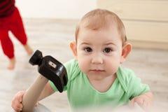 Baby mit Hammer beabsichtigen zu arbeiten stockfotografie