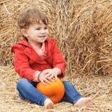 Baby mit Kürbisen auf einem Bauernhof Stockfotos