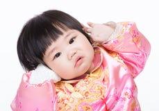 Baby mit Kleidung und Haben des traditionellen Chinesen lustiger Position Lizenzfreies Stockbild