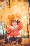 Baby mit Kranz im Herbstpark lizenzfreie stockbilder