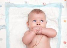 Baby mit Lügen und Blick der blauen Augen auf die Kamera Lizenzfreie Stockbilder