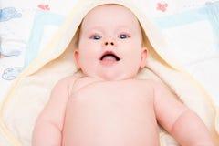 Baby mit Lügen und Blick der blauen Augen auf die Kamera Lizenzfreies Stockbild