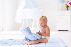 Baby mit Milchflasche in der sonnigen Kindertagesstätte Stockbilder