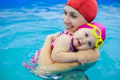 Baby mit Mutter im Pool Stockfotografie