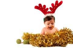 Baby mit offenem Mundkleid als Ren, das goldenes Lametta betrachtet Lizenzfreie Stockfotografie