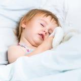 Baby mit Spielwaren im weißen Bett Lizenzfreies Stockfoto