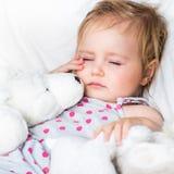 Baby mit Spielwaren im weißen Bett Stockfoto