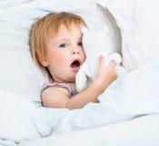 Baby mit Spielwaren im weißen Bett Stockbild