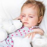 Baby mit Spielwaren im weißen Bett Lizenzfreie Stockfotos
