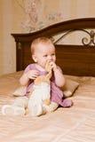 Baby mit Spielzeug im rosa Kleid auf Hintergrund des Innenraums Lizenzfreies Stockbild