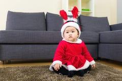 Baby mit x mas-Behandlung und Sitzplätze auf Teppich Stockfotografie