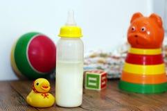 Baby mjölkar och leksaksamlingen royaltyfria foton
