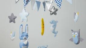 Baby mobiel met blauw hand-gestikt dier en vogelspeelgoed met gele maan stock video