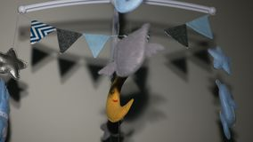 Baby mobile with blue hand-stitched animal and bird toys with yellow moon stock footage