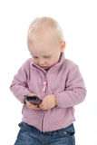 Baby with a mobile phone. The little girl playing with a mobile phone Royalty Free Stock Photography