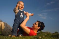 Baby, moeder, gras en hemel Stock Foto's