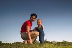 Baby, moeder, gras en hemel Stock Foto