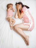 Baby with mom. Little girl with her mom playing on a bed - view from above Royalty Free Stock Photo