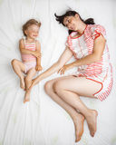 Baby with mom. Little girl with her mom playing on a bed - view from above Royalty Free Stock Photography