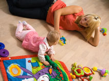 Baby with mom. Baby playing on floor with mom Stock Photography