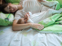 Baby with mom. Awake baby with sleeping mom in a bed Royalty Free Stock Photo