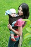 Baby with mom in baby carrier. Mother carrying her baby in sling - baby carrier Royalty Free Stock Images