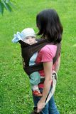 Baby with mom in baby carrier. Mother carrying her baby in sling - baby carrier Royalty Free Stock Image
