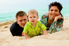 Baby, mom and dad on sand Stock Images