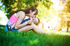 Baby and mom in a greenl summer park Stock Image