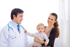 Baby on mom hand touching stethoscope of doctor Stock Images