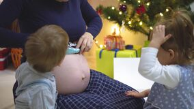 Two children grope listen and kiss the belly of a pregnant mother stock footage