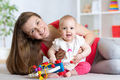 Baby with mom. Mother and daughter indoor. Little girl and woman play together. Happy baby with mom. Mother and daughter indoor. Little girl and women play stock photo